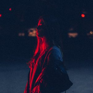 Woman carrying bag in dark in a red-light district - survival sex