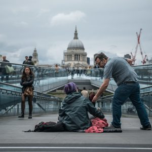 Homeless person affected by Austerity sitting in front of At Paul's Cathedral